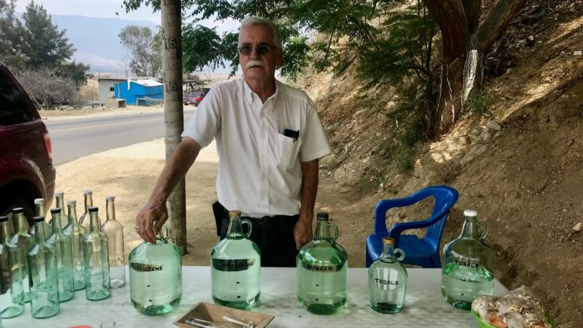 Mezcal tour guide Alvin Starkman stands with bottles