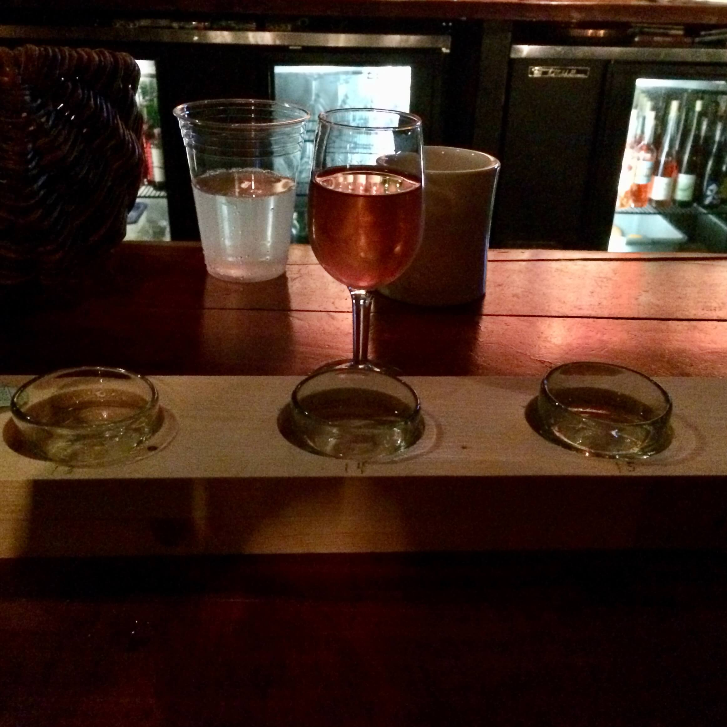 Three glass mezcal copitas and a glass of Rose wine on the bar at King Bee Lounge