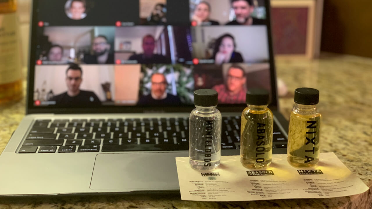 Three one ounce bottles of mezcal and a laptop during a virtual tasting