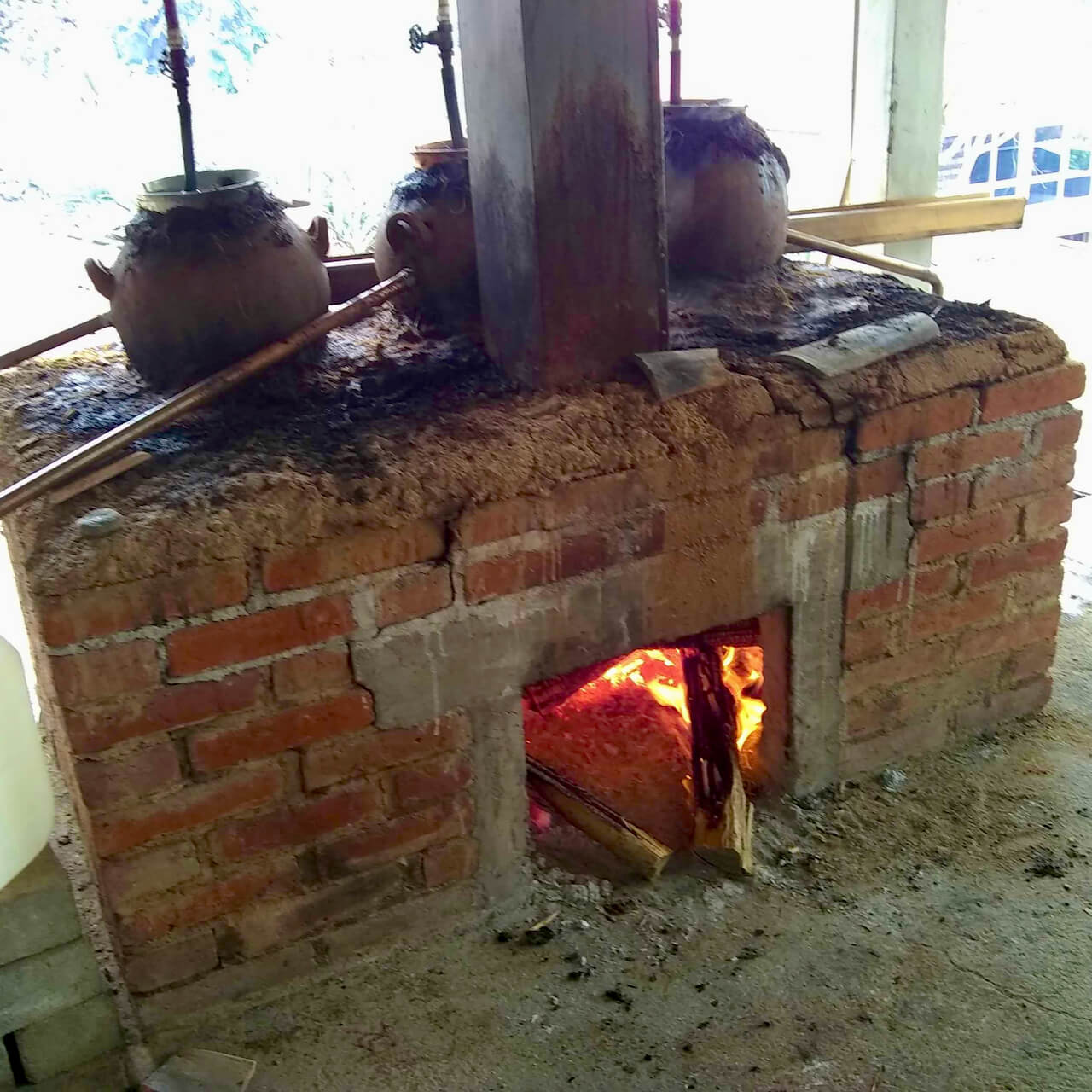 A mezcal still with one source of fire and three stills
