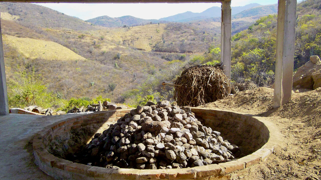 An empty mezcal oven with lava rocks and a wide landscape in the background